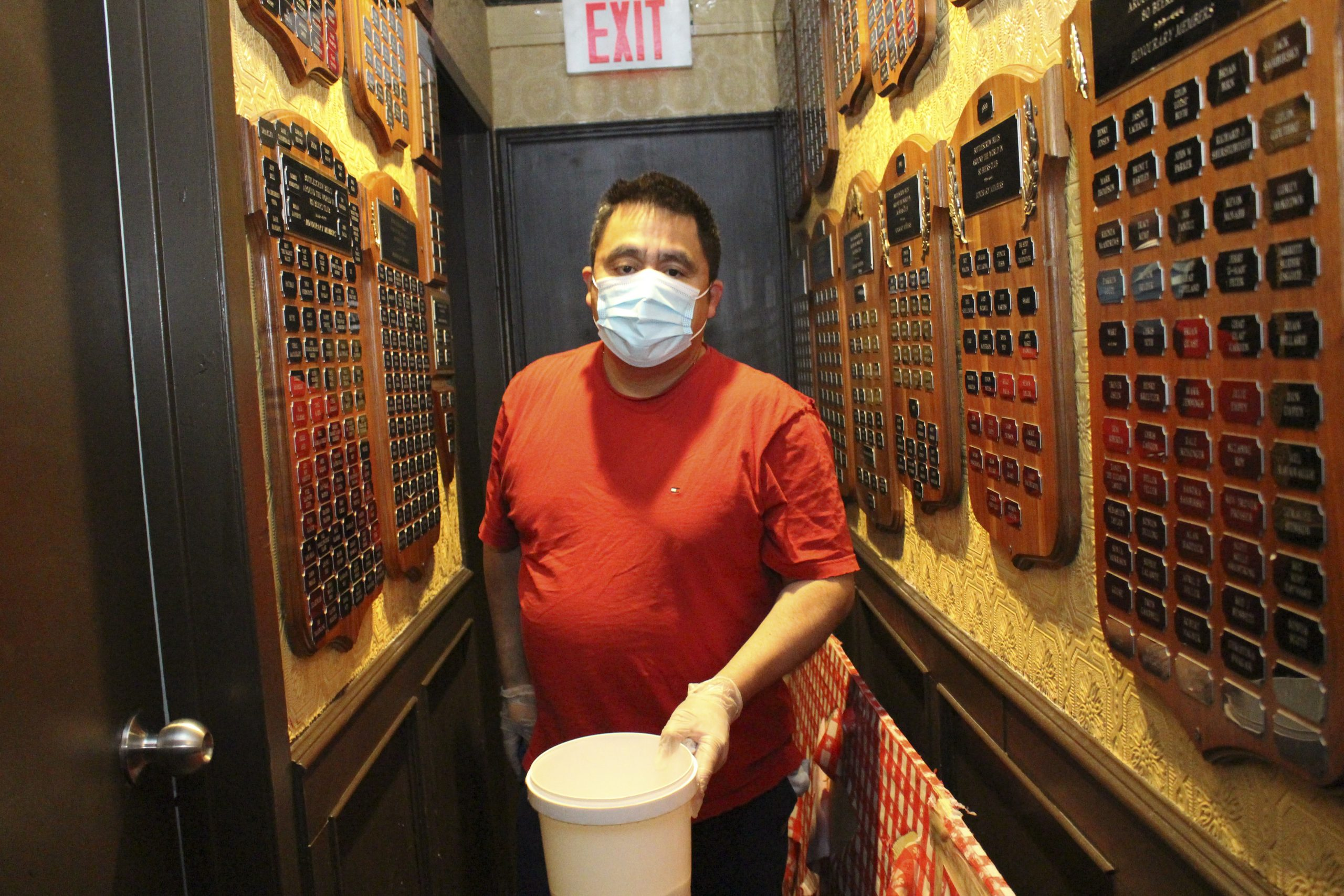 Francisco Melgar walks from one bathroom to the other in the hall that recognizes patrons that have been ÒAround-The-World-in-80-BeersÓ in Bottlescrew BillÕs in Calgary on April 15, 2021. ÒAround-The-World-in-80-BeersÓ is a contest that Bottlescrew BillÕs has where a patron try to fill out a passport that features their selection of beers from around the world. (Photo by Alejandro Melgar/SAIT)