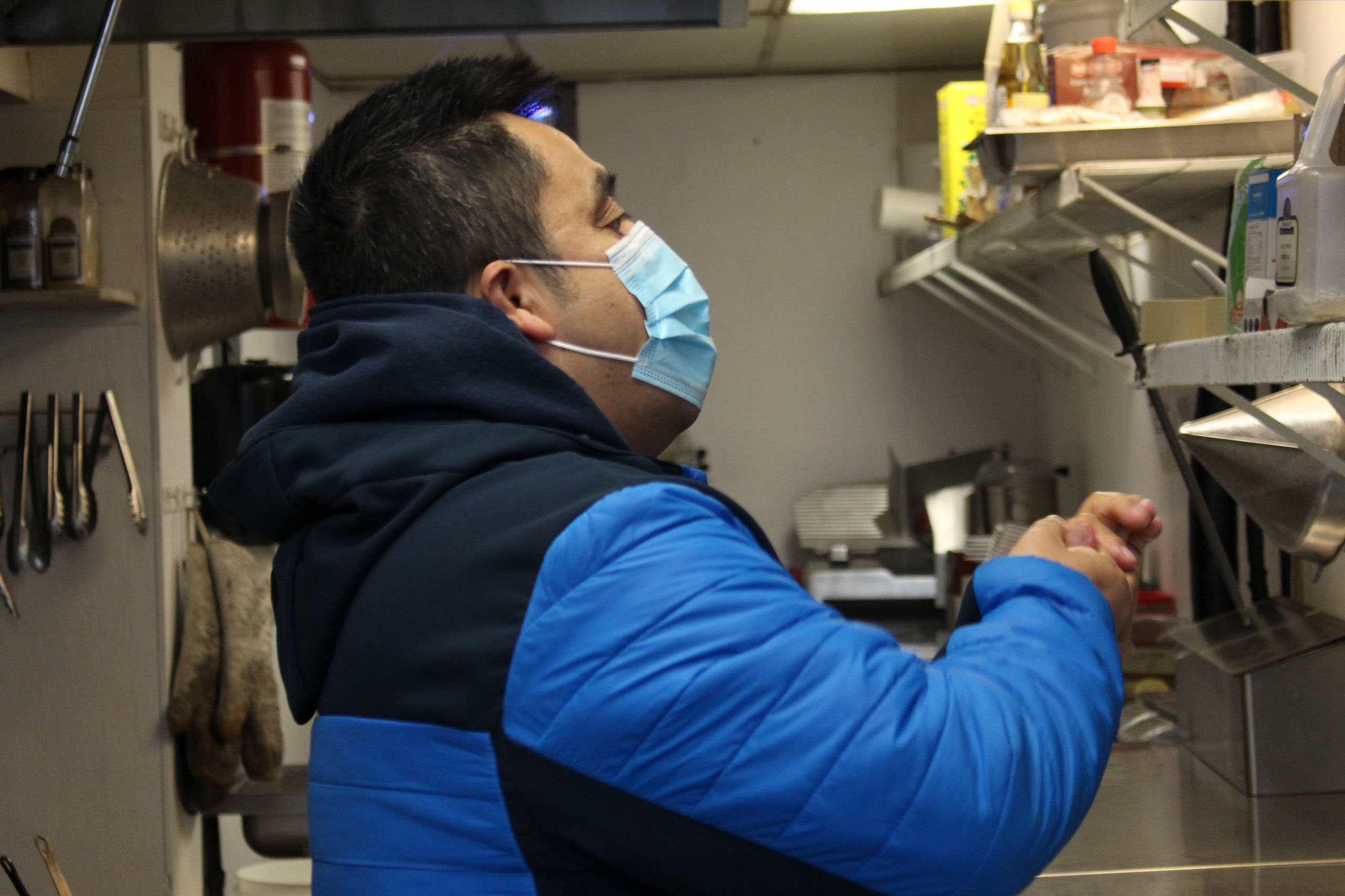Francisco Melgar applies hand sanitizer before putting on gloves in the kitchen of Bottlescrew Bill's before starting his cleaning duties in Calgary on April. 15, 2021. Melgar was laid off officially from the Sheraton Eau Claire, the place he worked for for 15 years, back in October of 2020, after being on a leave as a result of the COVID-19 pandemic. He was the assistant to the power engineer. (Photo by Alejandro Melgar/SAIT)
