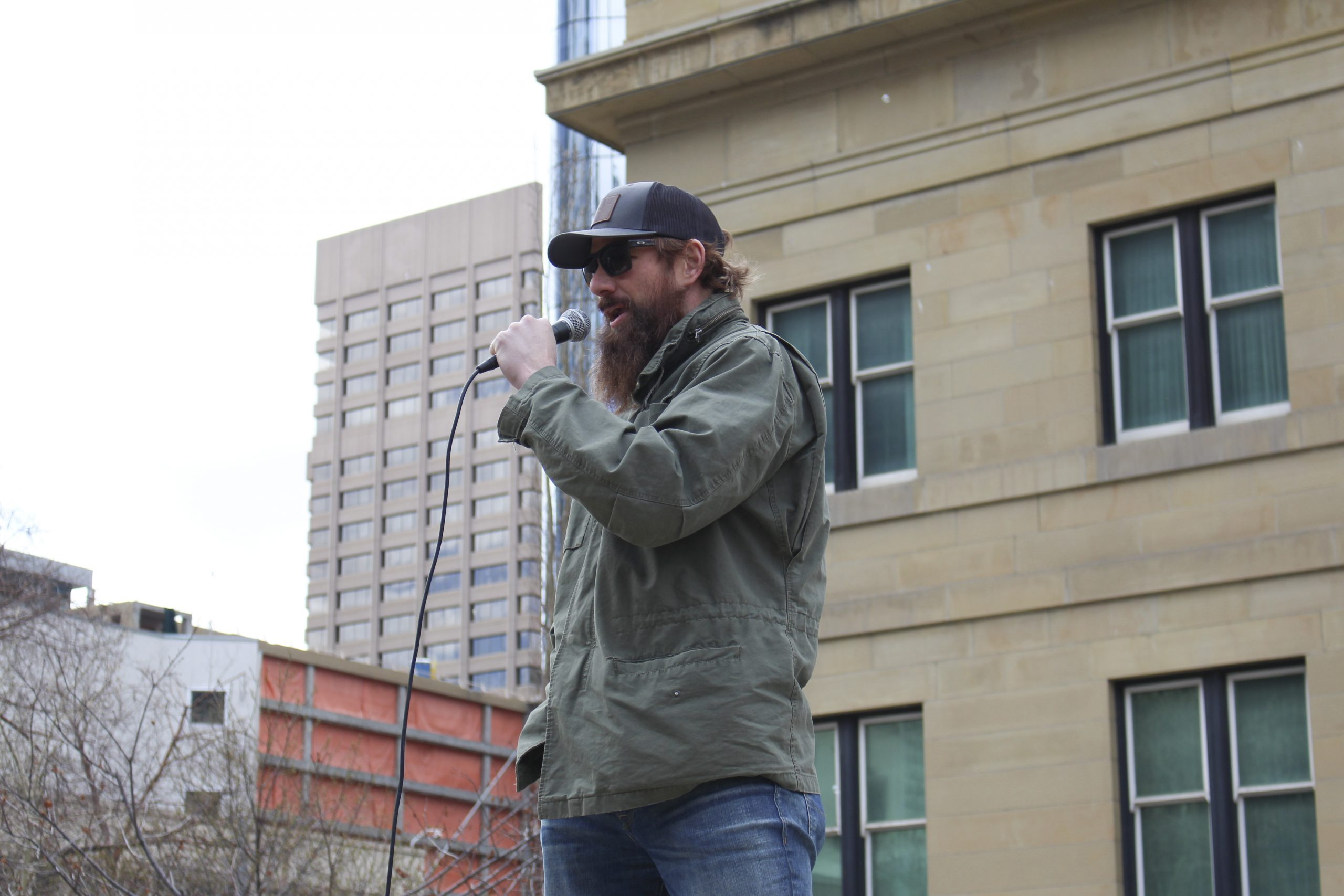 """Travis Cain speaks to a crowd as the emcee for the """"Save Small Business"""" rally at Courthouse Park in downtown Calgary on April 11, 2021. Cain is a volunteer with Freedom4Canada, and he regularly starts the rallies as the opening speaker. Freedom4Canada is also Freedom Corp., a corporation that sponsors different rallies, like the Save Business Rally hosted by Calgary Freedom Central, and these rallies express disdain for mask usage, vaccines, the COVID-19 testing method, and compliance with the government and the enforcement of said closures.(Photo by Alejandro Melgar/SAIT)"""