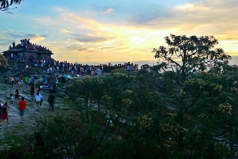 Pôr do sol em tom de amarelo com muitas pessoas embaixo assistindo