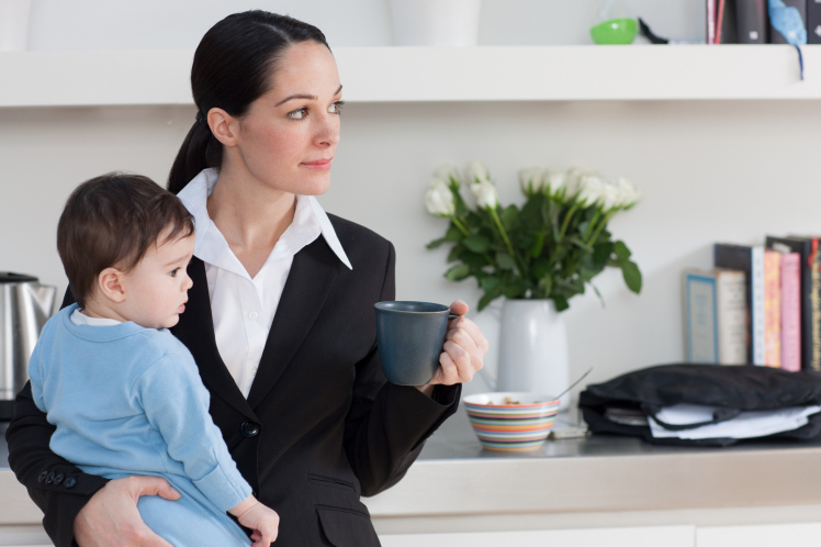 Businesswoman holding baby son and coffee cup