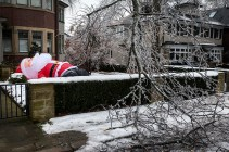 An inflatable Santa Claus decoration, deflated due to a power outage, is pictured behind a fallen tree limb after an ice storm hit Toronto