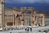 Tre siriani camminano a fianco del sito archeologico di Palmira, in Siria. (JOSEPH EID/AFP/Getty Images)