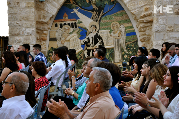 Members of the Syriac community applaud during a ceremony in Bethlehem to honour recent graduates from high school and college (MEE/Emily Mulder)