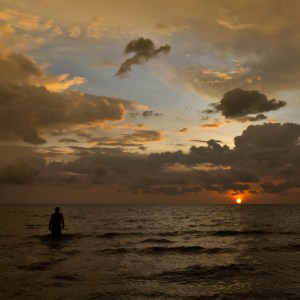 At Otres Beach in Cambodia, a man wades out to sea as the sun casts its final rays over the ocean.
