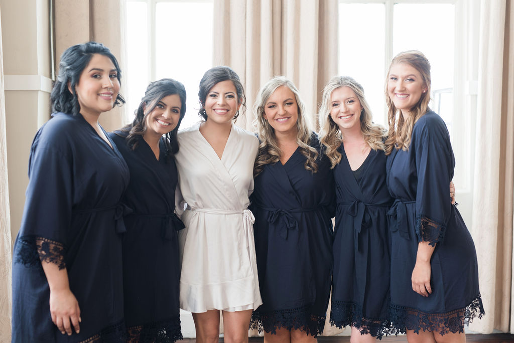 Bridal party in navy blue robes: Dusty Blue and Blush Wedding at The Room on Main featured on Alexa Kay Events!
