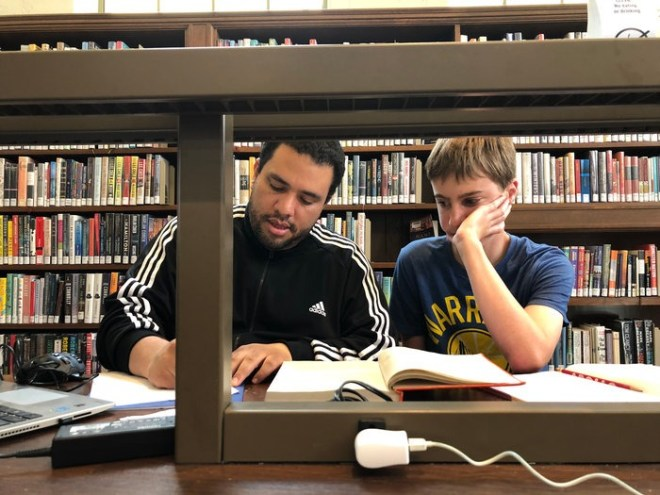 Felix tutoring one on one in a library