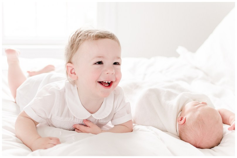All smiles for this naturally lit newborn session. All white monotoned bedroom provides the perfect backdrop for a distraction-free newborn session.