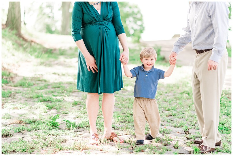 Emerald green maternity session at Libby Hill Park in Richmond Virginia. This family of three is welcoming a new baby in August. A two year old who loves to run is calmed down for a picture with games of jumping and freeze, singing songs and more!