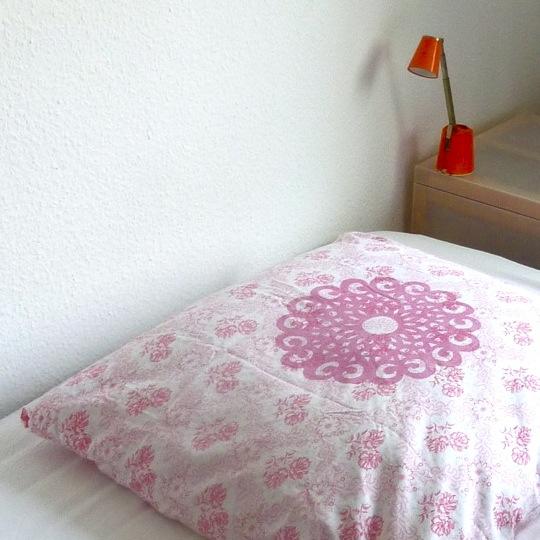 Kopfkissen Motiv Rosette: Dieses dekorative Ornament besticht durch seine Größe und Klarheit/ Flächigkeit. - von Hand gedrucktes Unikat - Größe: ca. 80 x 80 cm - Material: antike Kissenhülle mit rosa Streublumen, 100% Baumwolle - Druckfarbe: Pink - Logo-Aufdruck auf der Rückseite - mit Knöpfen - waschbar bis 60° C