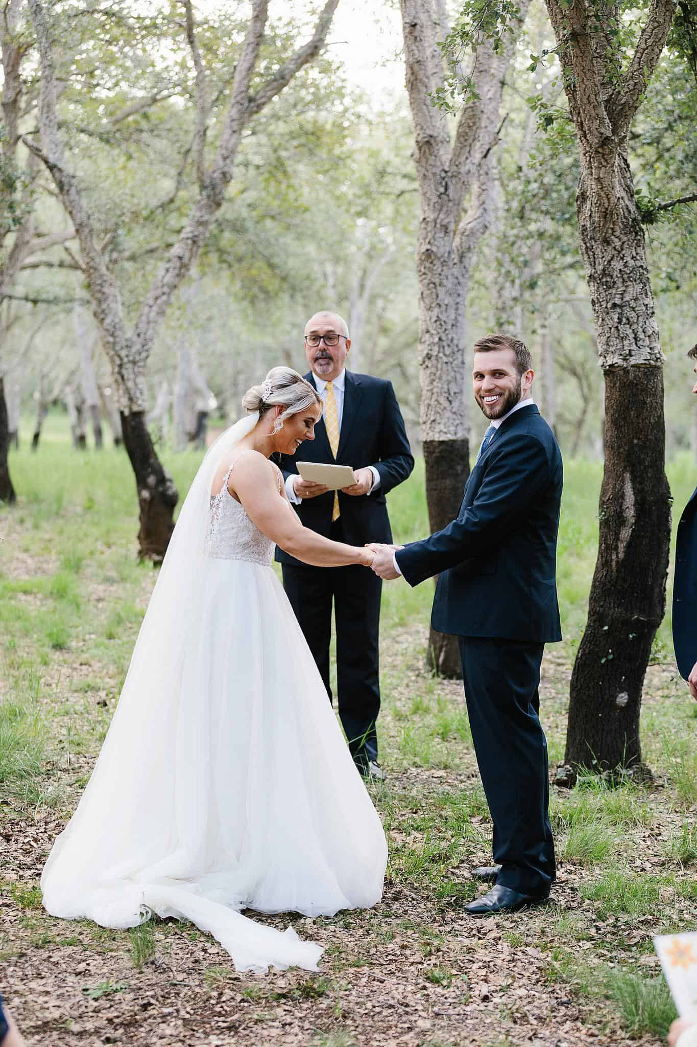 Bride and groom laugh with celebrant