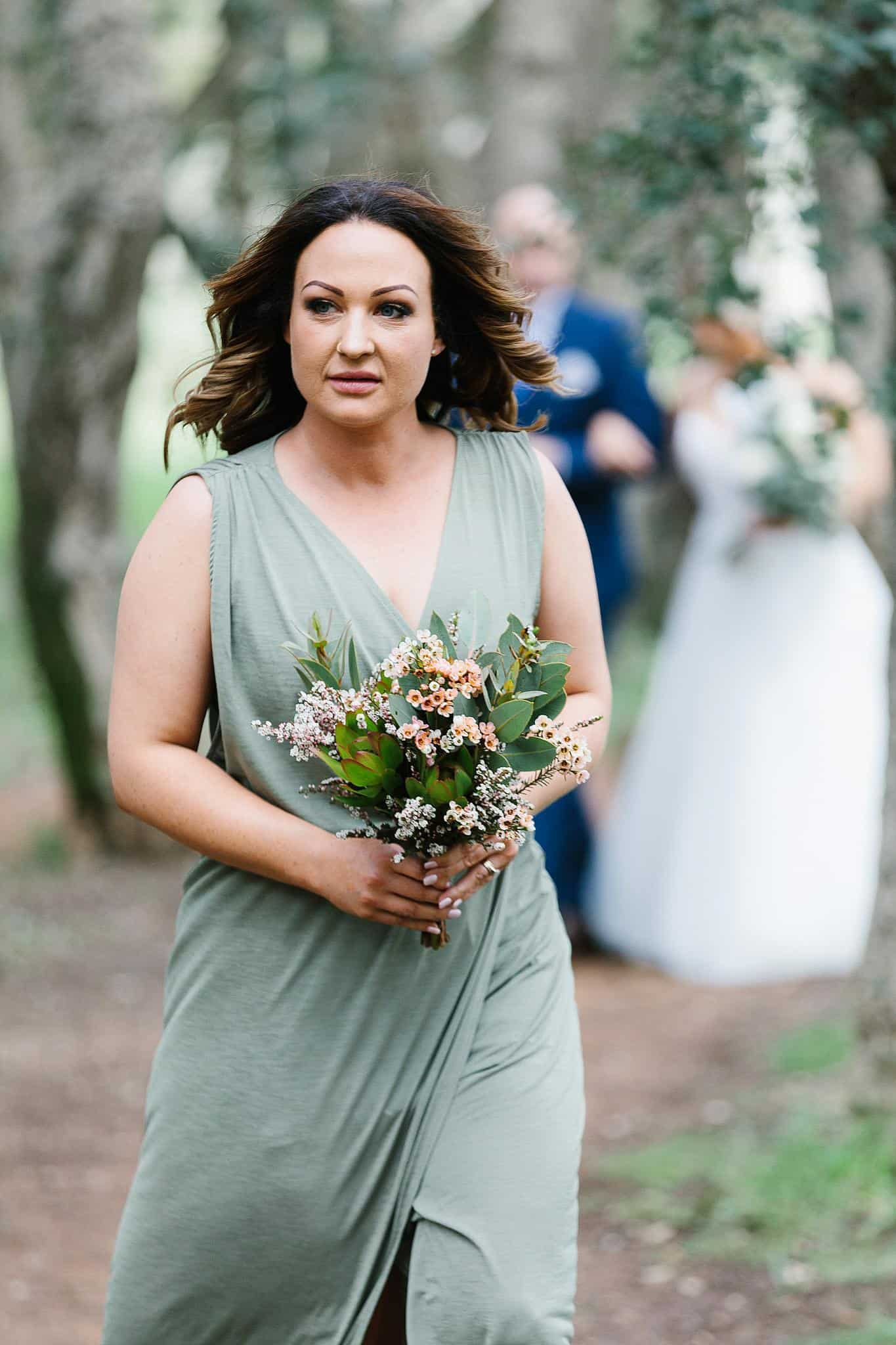 Bridesmaid walks with Father of the Bride and Bride behind