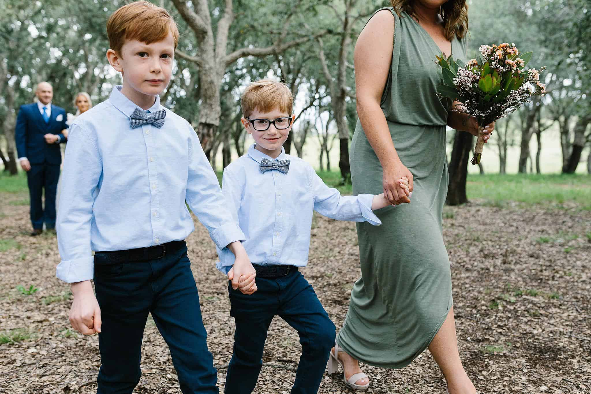 Ring bearers walk with bridesmaid down the aisle