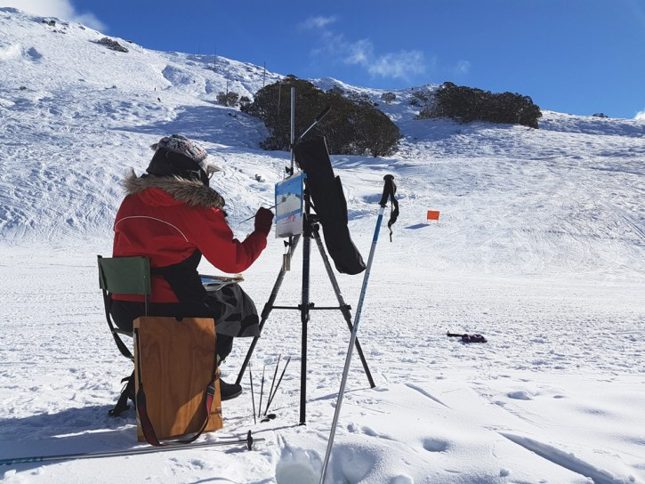Image of Alexandra Sasse painting in the snow at Falls Creek