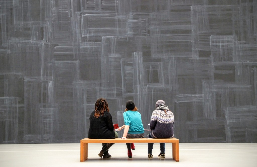 Image of three people seated on bench in art gallery