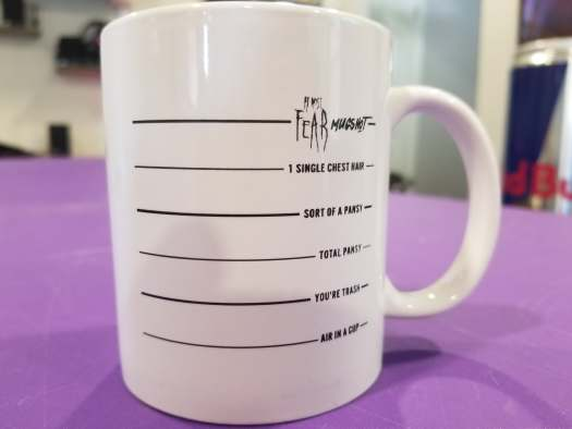 "At Most Fear's ""Mugshot"" merch  is a mug with lines on it to mark alcohol consumption."