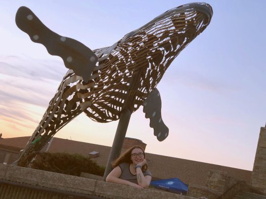 An image of Alexa at Jones Beach with a whale sculpture.