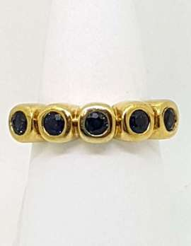 five black sapphires inline on 9 carat gold ring in cellular design