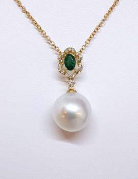 Pearl drop necklace on gold chain and oval emerald
