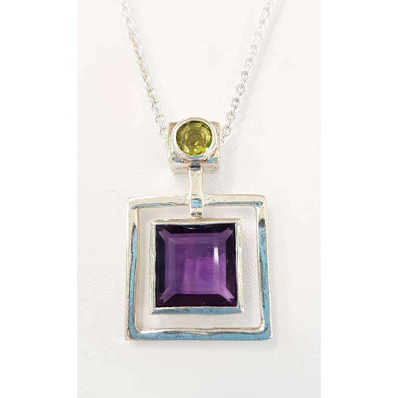 Square amethyst set in sterling silver framed setting with green period and silver chain necklace