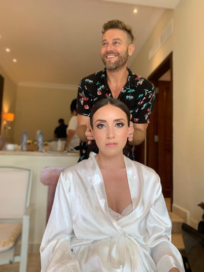 artist poses with bride after hair and makeup is done in dreams tulum