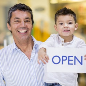 Dad and son holding an open sign