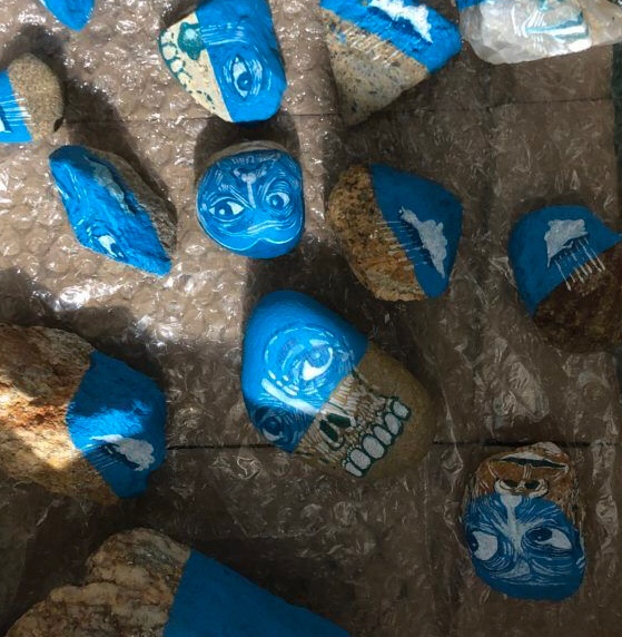 Faces drawn on blue painted rocks