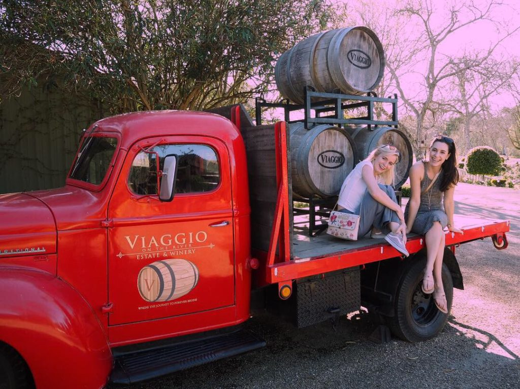 sitting on the back of a red truck at the Viaggio winery