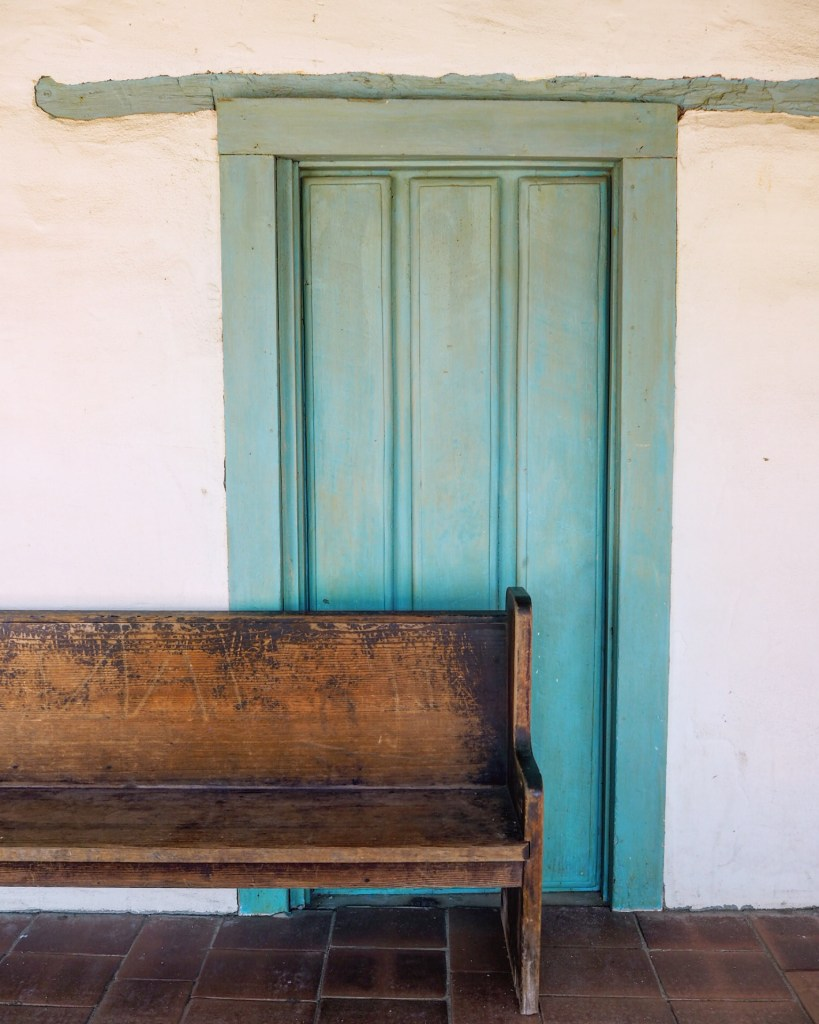 bench and a turquoise door
