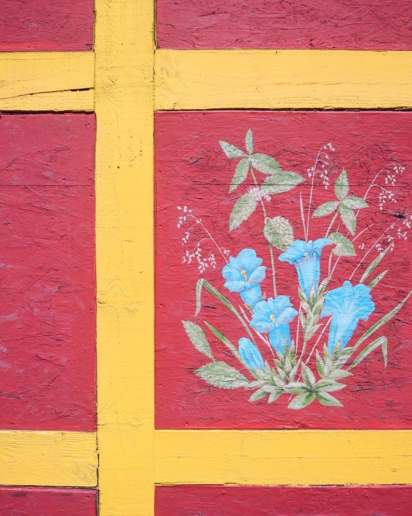 close up of blue flowers painted on a house