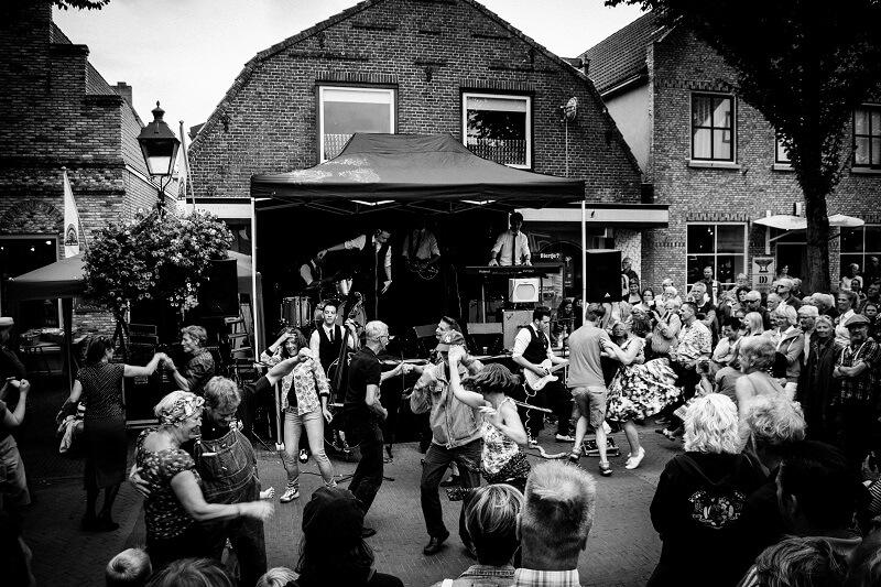 Dansende mensen op straat tijdens een optreden van The Hot Dogs Coverband tijdens het Rock and Roll Street Terschelling festival in september 2016.