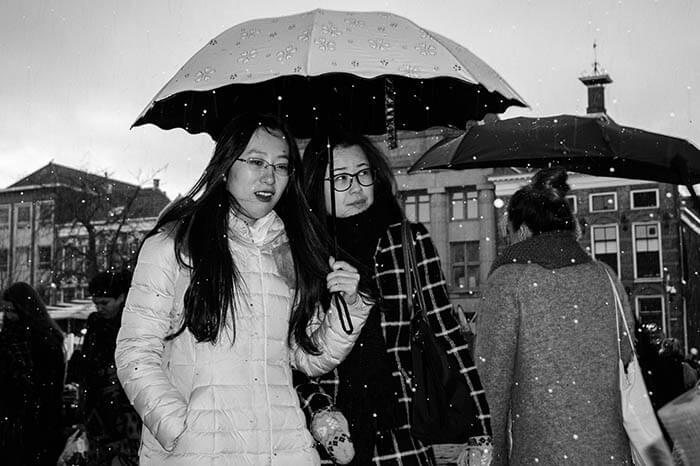 Vrouwen onder een paraplu tijdens een winterse bui in de stad Groningen.