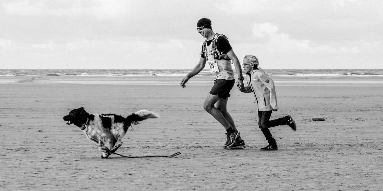 Berenloper samen met hond en kind op het strand.