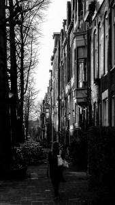 Een vrouw loopt weg van de camera op een straat in Groningen.