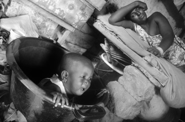 Isatou is left in a bucket on a hot day as an effective method of childcare.