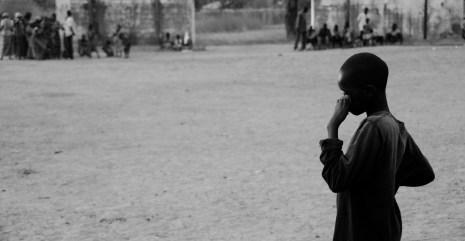 A boy watches a football match.