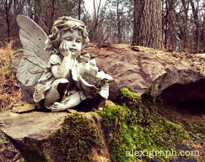Photo of a cherub statue with head in hand, sitting on a rock in the woods