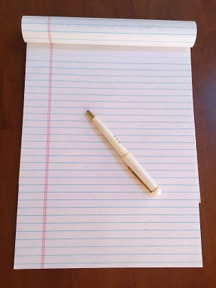 A legal pad turned to a blank sheet, with a pen
