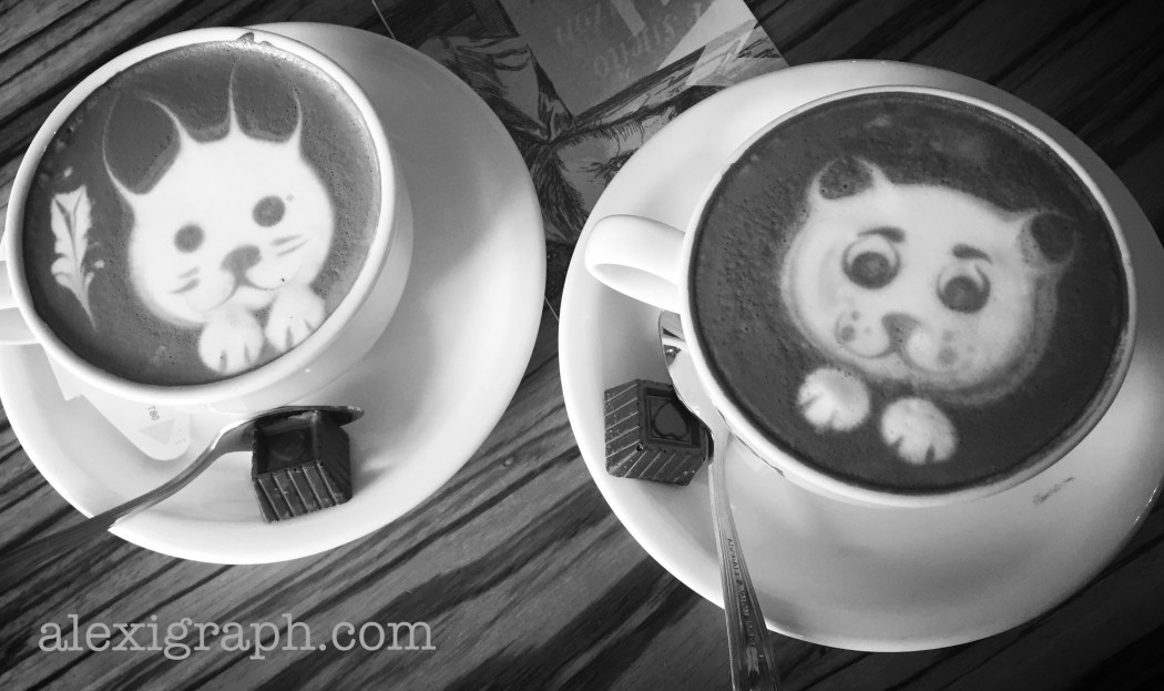 Two mugs of cappuccino with animals drawn in the froth