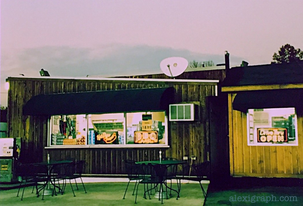Photo of a convenience store with food signs and tables outside