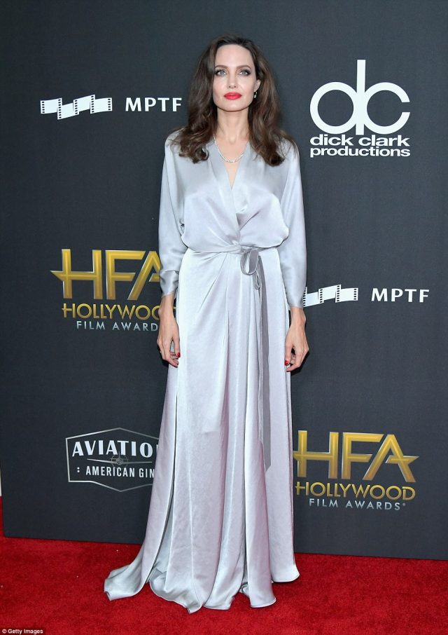 Angelina Jolie is picture perfect in a plunging silver wrap dress while leading the glamour for star-studded Hollywood Film Awards