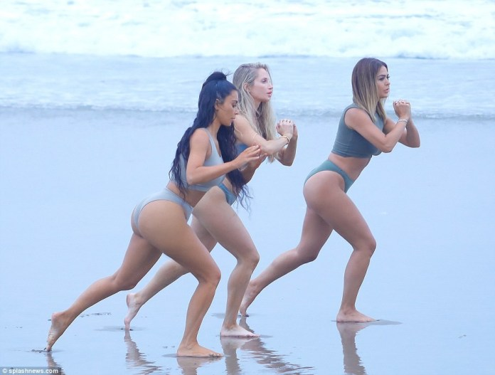 Kim K parades her enviable curves in crop top and briefs for yoga session on the beach (Photos)