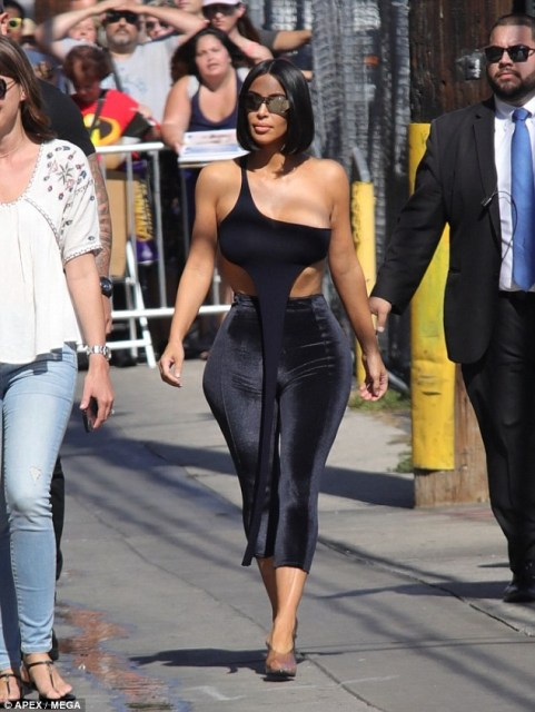 Kim Kardashian causes a stir in Los Angeles as she steps out in skintight velvet pants with barely-there crop top (Photos)