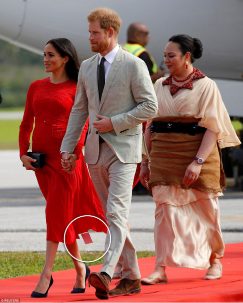 Meghan Markle makes fashion faux pas as a return label is seen hanging from her dress as she touches down in Tonga with Prince Harry