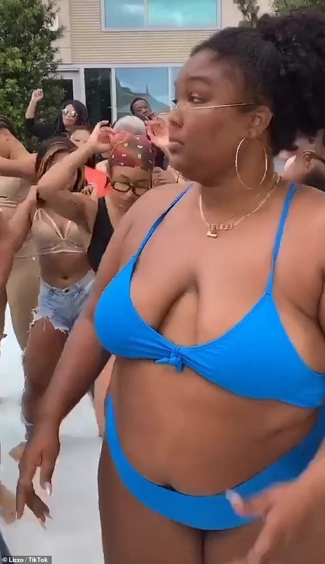 Lizzo shows some skin in a blue bikini while dancing with friends at a pool party