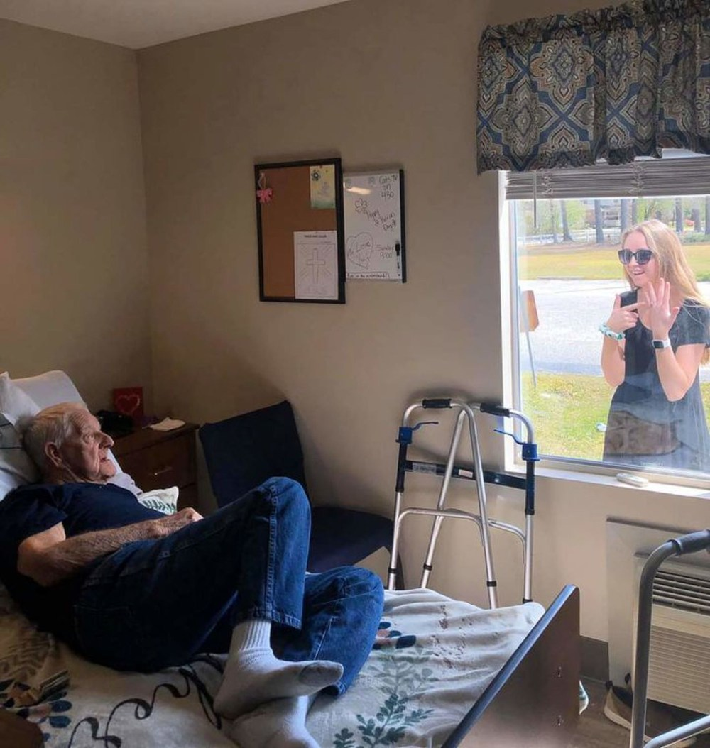 Coronavirus: Heartbreaking photos show woman showing off her engagement ring to her grandfather through the window of his nursing home because she can