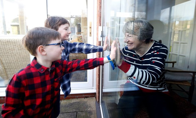 Coronavirus: Two brothers talk to their self isolating grandma through a window on Mother's day (photographs)