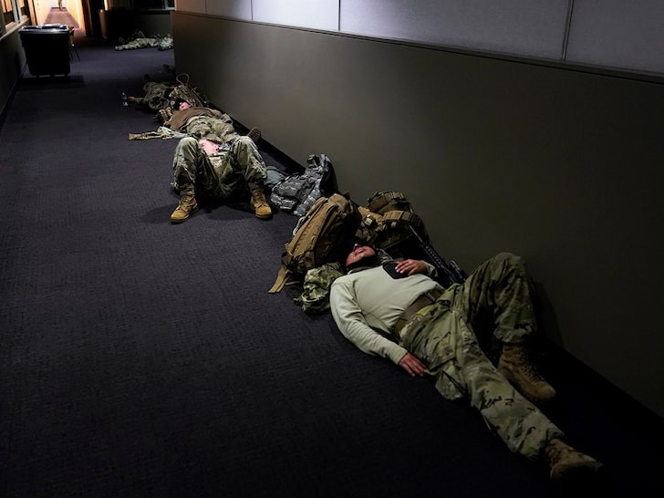 Exhausted US National Guards sleep on Capitol floor with their weapon by their side