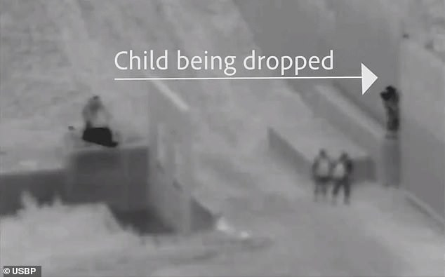 Migrant smuggler drops a Ghanaian child, 2, from top of 18-foot-high US-Mexico border wall into the arms of his father waiting on the other side of the wall (video)