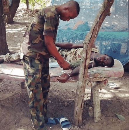 Trending photo of a sick Nigerian soldier receiving treatment on mattress supported by branches while his IV fluid hangs from a tree